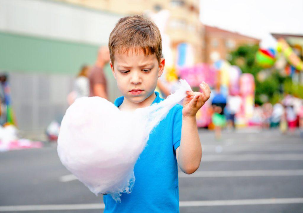 ילד אוכל מדוכן צמר גפן מתוק